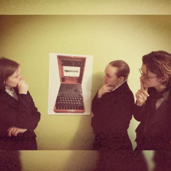 Uczniowie patrzą na obrazek, który przedstawia maszynę Turinga