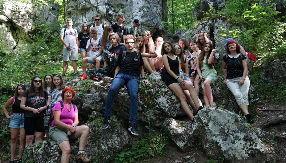 Grupowe zdjęcie uczniów. Stoją i siedzą na skale a w tle są lasy.